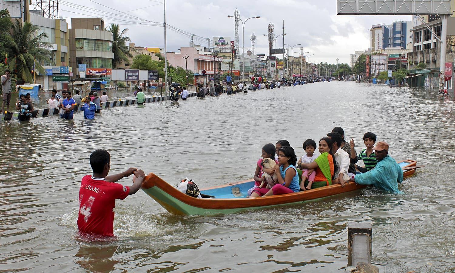 People travel on a boat as they move to safer places through a flooded road in Chennai, India, December 2, 2015. — Reuters