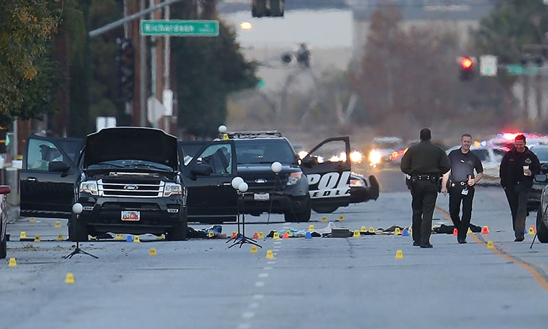 Law enforcement officials continue their investigation around the Ford SUV vehicle that was the scene. —AFP