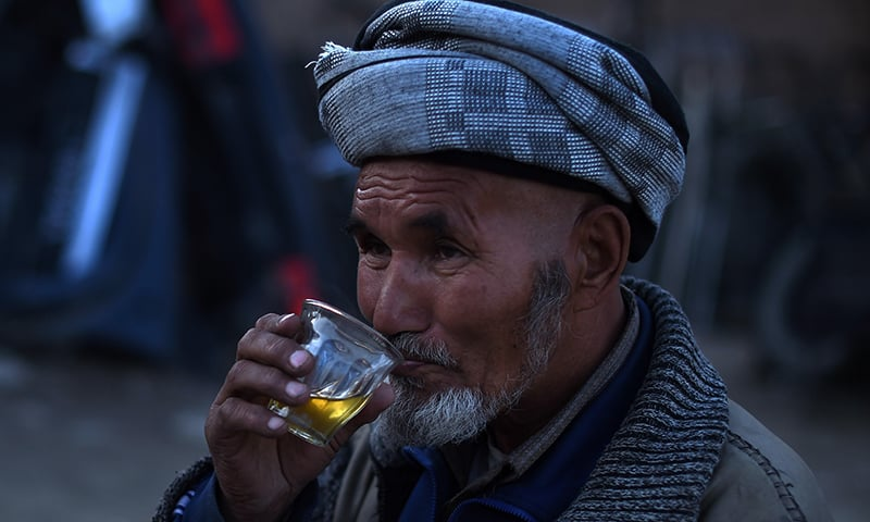 An Hazara Afghan drinks tea at a second hand vehicle parts shop in the Dasht-E-Barchi Hazara neighbourhood of Kabul. — AFP