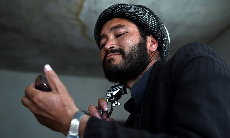 An Hazara Afghan trims his beard inside a local restaurant in the Dasht-E-Barchi Hazara neighbourhood of Kabul. — AFP