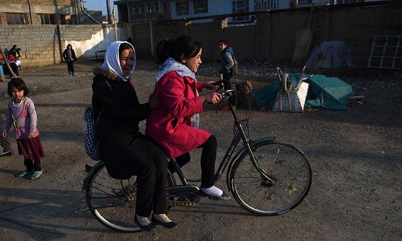 Young Hazara Afghan children ride a bicycle in the Dasht-E-Barchi Hazara neighbourhood of Kabul. — AFP