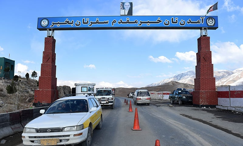 "Afghan local vehicles with passengers onboard pass under the main gate, on which is written ""Safe Journey"", on the highway to Maidan Wardak province west of Kabul. — AFP"