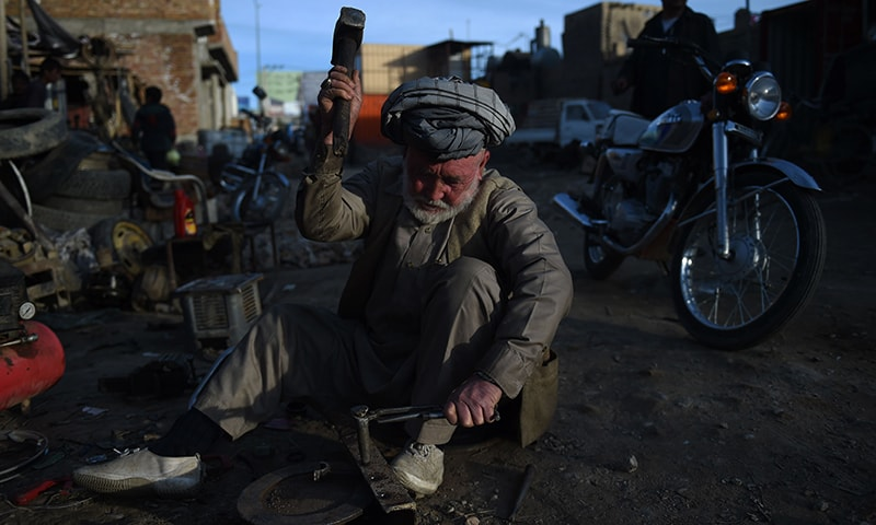 An Hazara Afghan mechanic works at a secondhand car parts shop in the Dasht-E-Barchi Hazara neighbourhood of Kabul. — AFP
