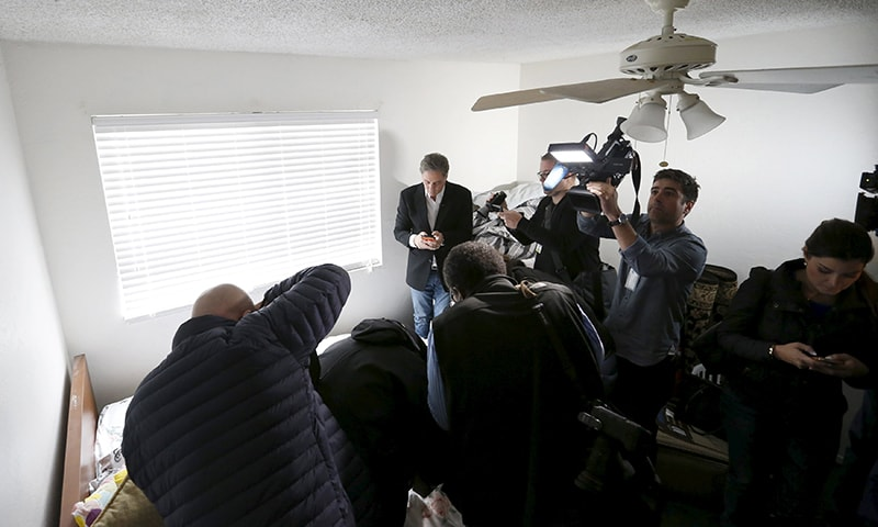 Members of the media are seen inside the home of the suspects. ─ Reuters