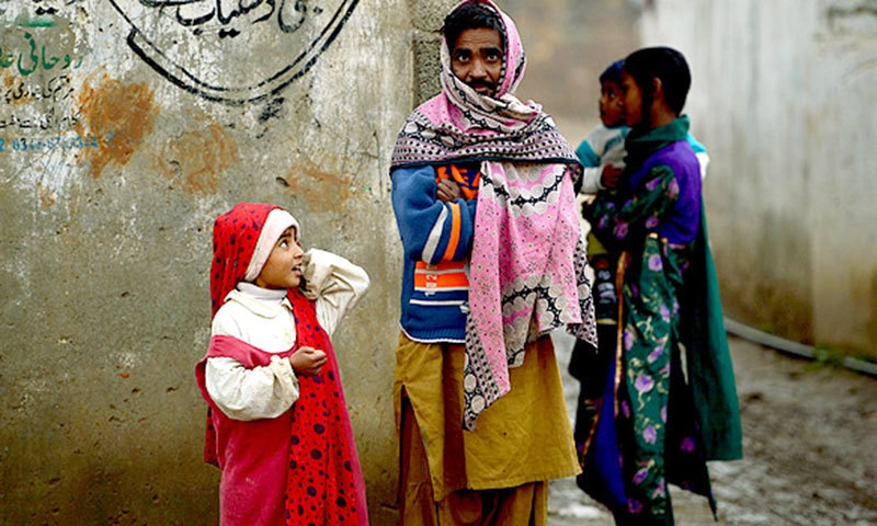 A Christian family stands outside their home in the run-down area of Mehrabad on the outskirts of Islamabad. —AFP