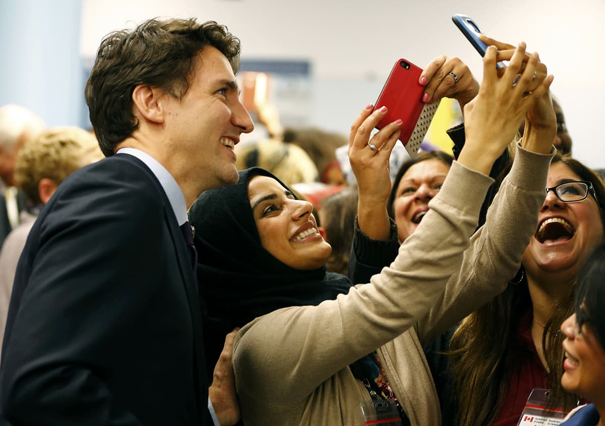 A Syrian refugee taking a selfie with the Canadian PM ─ Reuters