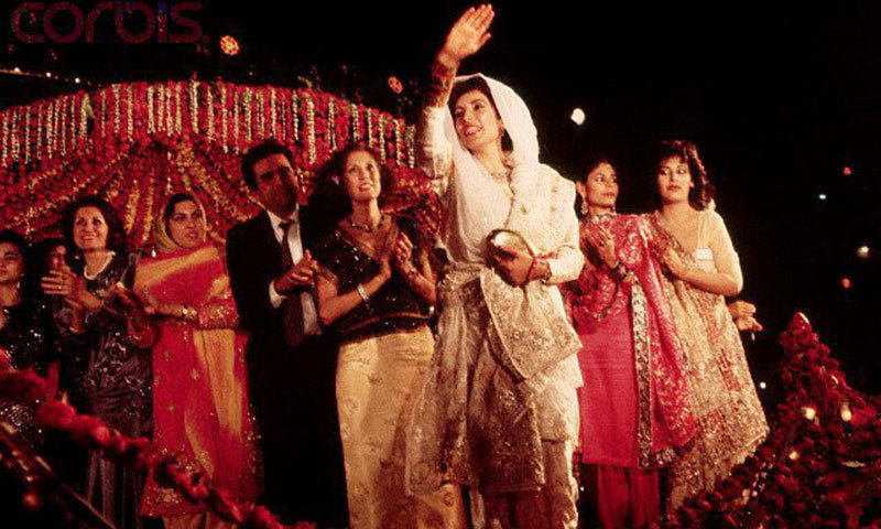 Benazir Bhutto waves to the crowd from the stage at her wedding celebrations held in Karachi's Lyari area (1987).
