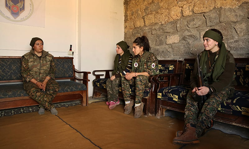 """Thabirta Samir (L), the head of the battalion of Syriac Christian women called the """"Female Protection Forces of the Land Between the Two Rivers"""" fighting the Islamic State group, talk with her team. — AFP"""