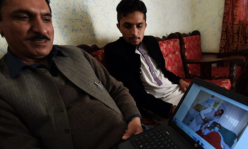 Momen Khan (L), father of student Waheed Anjum, who survived the APS massacre of December 16, 2014, the deadliest terror attack in Pakistan's history, shows a photograph of his injured son in hospital during an interview at their home in Peshawar. — AFP