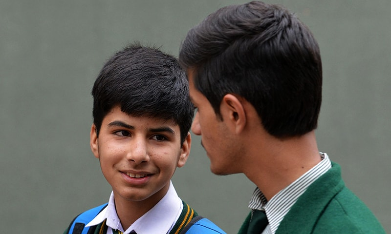 Mubashir Subhan, (L), a student who survived the Peshawar Army Public School massacre of December 16, 2014, the deadliest terror attack in Pakistan's history, chats with a friend at the army-run school in Peshawar. — AFP
