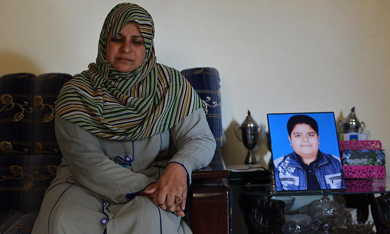 Andaleeb Aftab, a chemistry teacher at the army-run school where she lost her son Huzaifa, scene of the APS massacre of December 16, 2014, the deadliest terror attack in Pakistan's history, sits alongside a portrait of Huzaifa during an interview with AFP at her residence in Peshawar. — AFP
