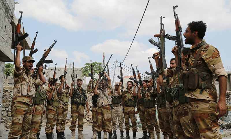 Soldiers loyal to Yemen's government raise their weapons following a training exercise. ─ Reuters