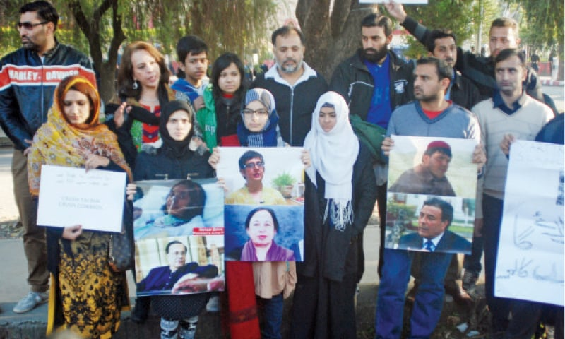 Members of civil society hold pictures of some others killed by terrorists outside Lal Masjid in Islamabad as they joined the first anniversary of the APS attack on Wednesday. The other picture shows Rangers personnel deployed outside Lal Masjid. — Photos by Ishaque Chaudhry