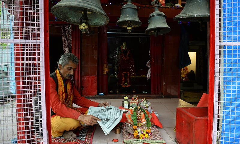 An Indian priest reads a Sanskrit newspaper as he sits inside a temple in New Delhi. — AFP