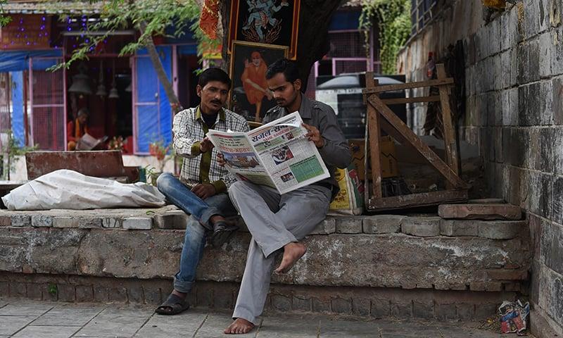 Indian men read a Sanskrit newspaper on a roadside near a temple in New Delhi. — AFP