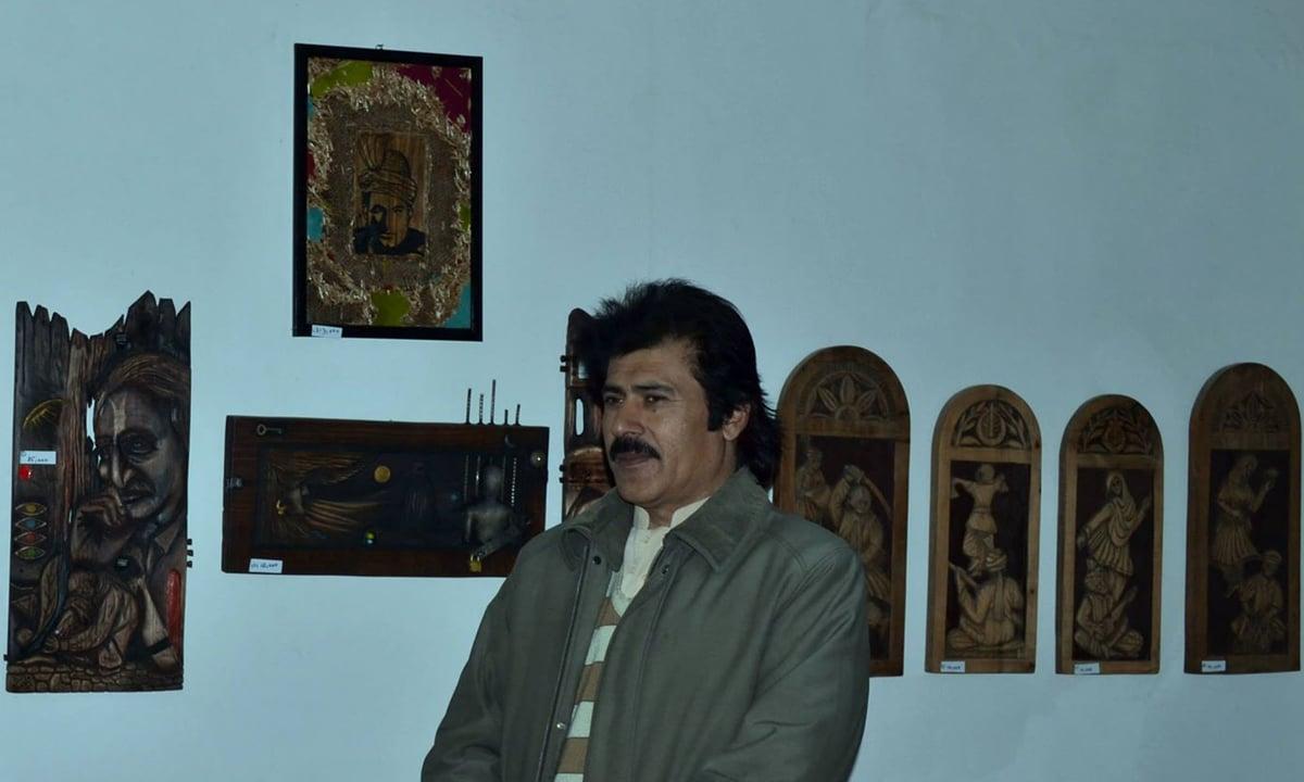 Nasar Sheen in front of a display of his art | Fazal Khaliq