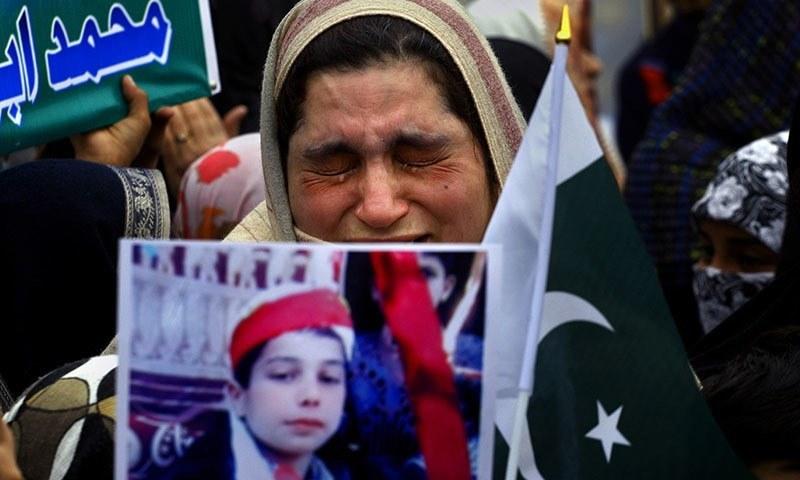 16 دسمبر 2014 کو پشاور کے آرمی پبلک اسکول حملے میں جاں بحق ہونے والے ایک بچے کی والدہ اس کی تصویر اٹھائے رو رہی ہیں۔