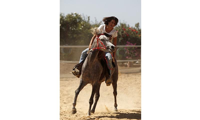 Raja Kheir rides a stray horse ─ AFP