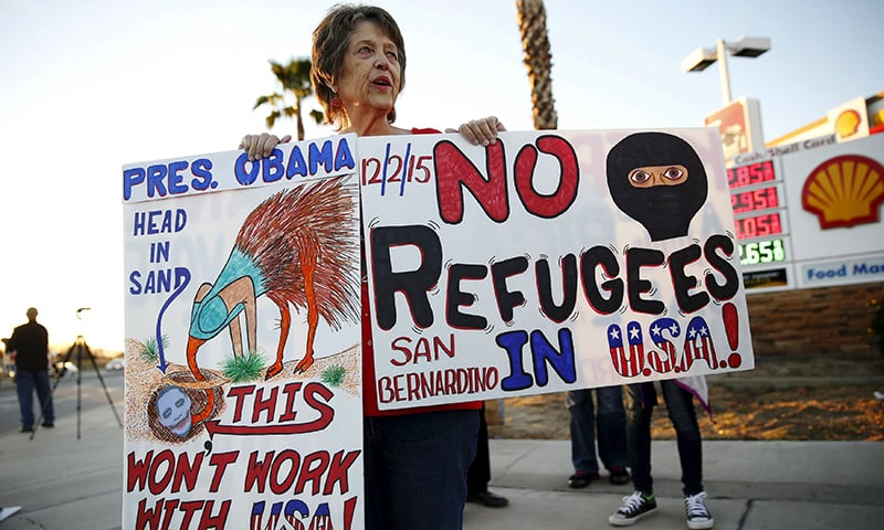 Deann D'Lean protests against IS and President Obama across from a makeshift memorial for victims of the San Bernardino shooting, ahead of President Obama's visit with the victims' families in San Bernardino, California on December 18, 2015.  —Reuters