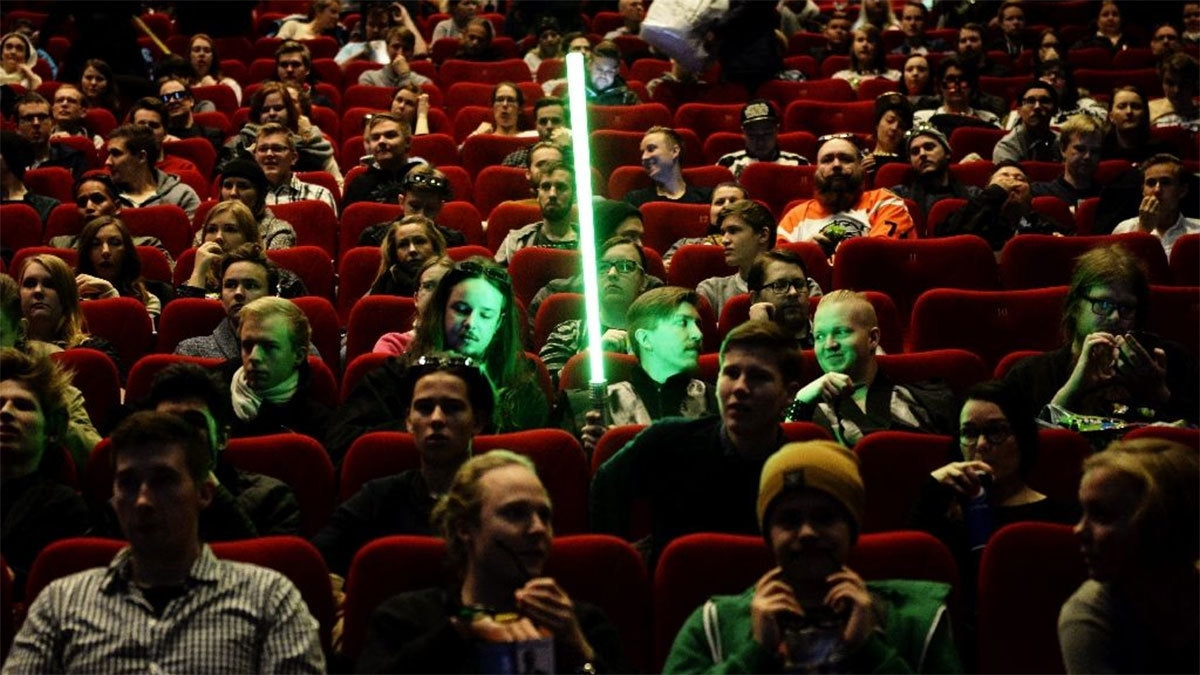 """A fan waits with his mock light sabre for the start of """"Star Wars: The Force Awakens"""".─AFP"""
