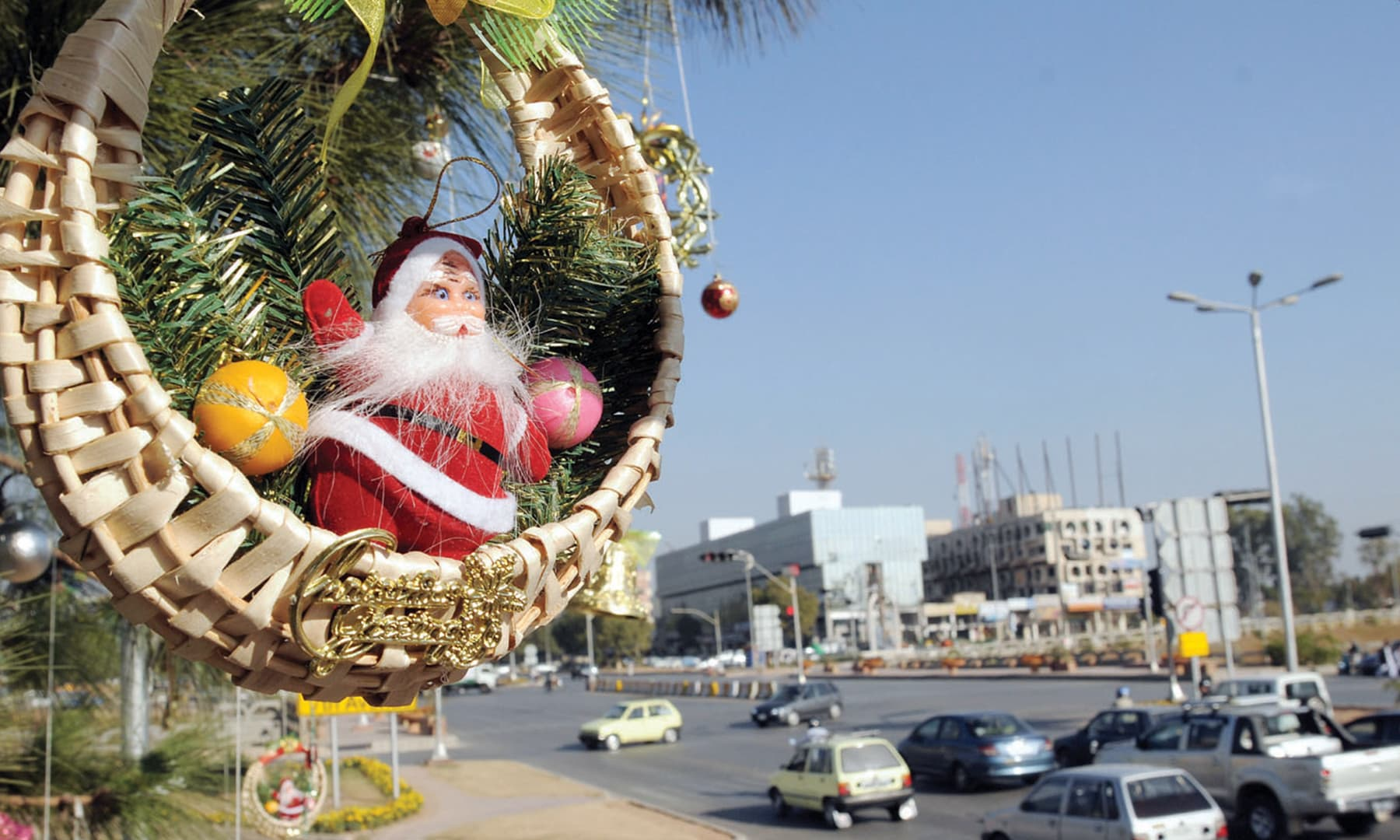 A decorative Christmas ornament hangs from a tree at Jinnah Avenue in Islamabad; the road has been decorated with Christmas buntings and lights | White Star