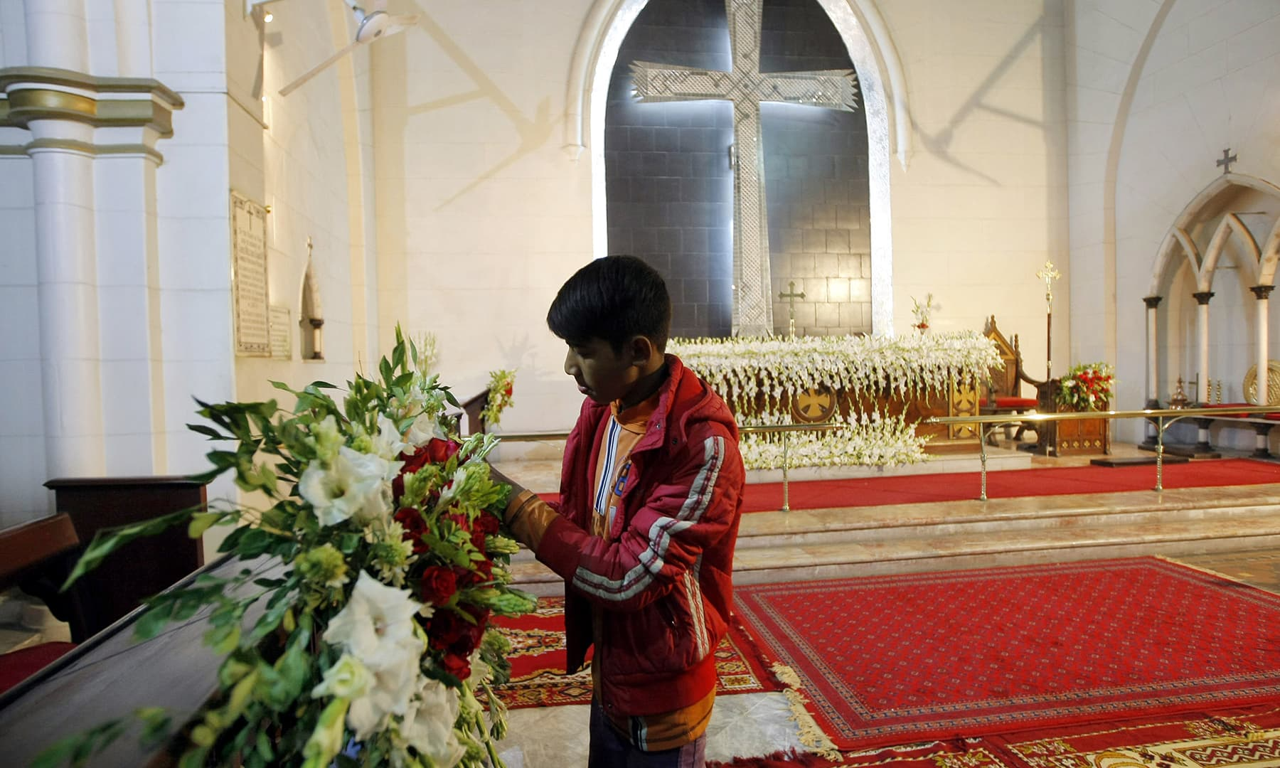 On Christmas eve, a young boy arranges the flower decorations at the Saint John's Church in Peshawar | White Star