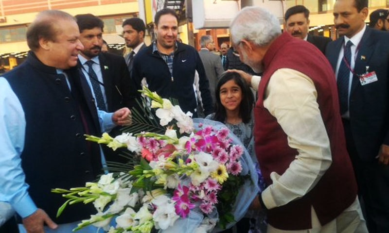 Modi receives flowers from a young girl on his arrival at Lahore airport.─Photo: Indian MEA spokesman's Twitter profile