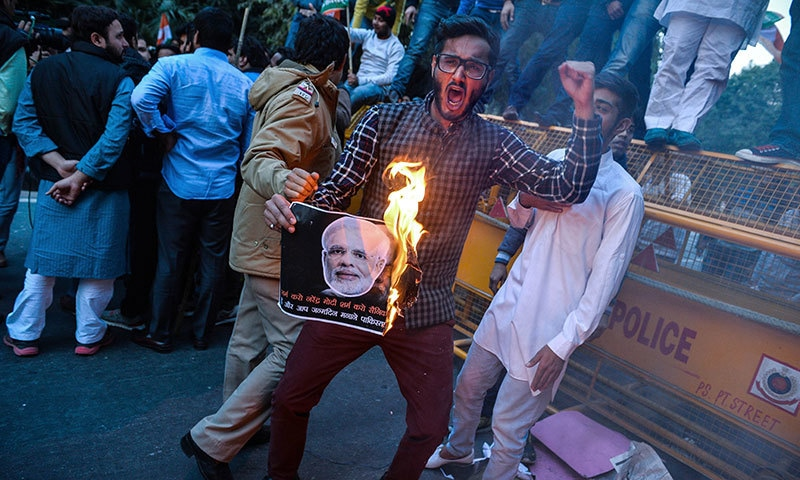An activist of the Indian Youth Congress (IYC) burns a poster with an image of Indian prime minister Narindra Modi as he shouts anti-government slogans during a protest of Modi's visit to Pakistan.─AFP