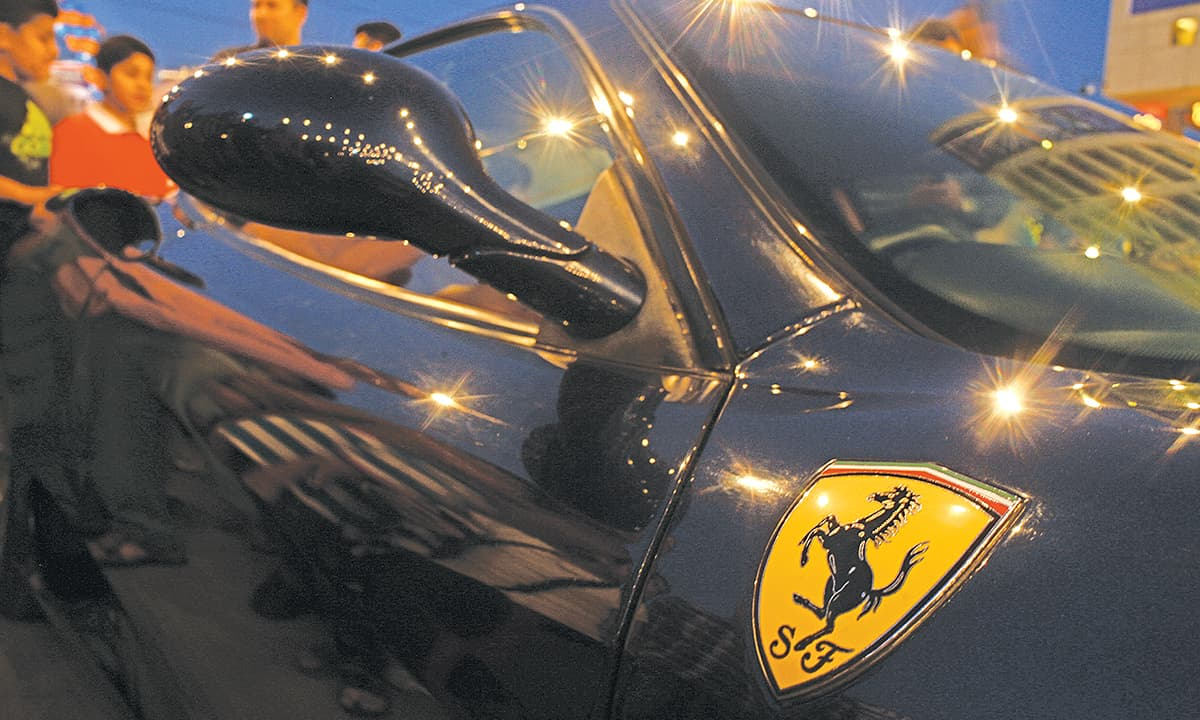 A gleaming Ferrari  attracts visitors at a car show