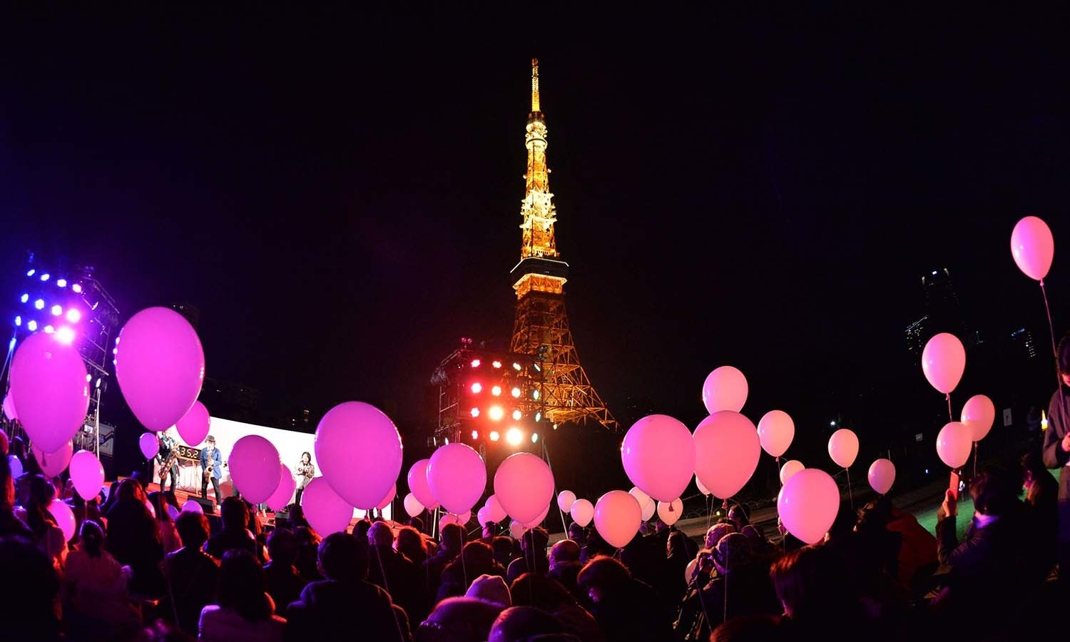 People gather to release balloons to celebrate the New Year during an annual countdown ceremony at the Prince Park Tower in Tokyo on December 31, 2015.  More than 1,000 balloons were to be released into the air, carrying with them new year wishes.  AFP PHOTO / KAZUHIRO NOGI