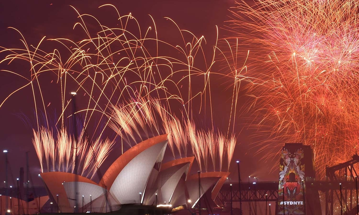 New Year's Eve fireworks erupt over Sydney's iconic Harbour Bridge and Opera House during the traditional fireworks show on January 1, 2016. AFP PHOTO / Peter PARKS
