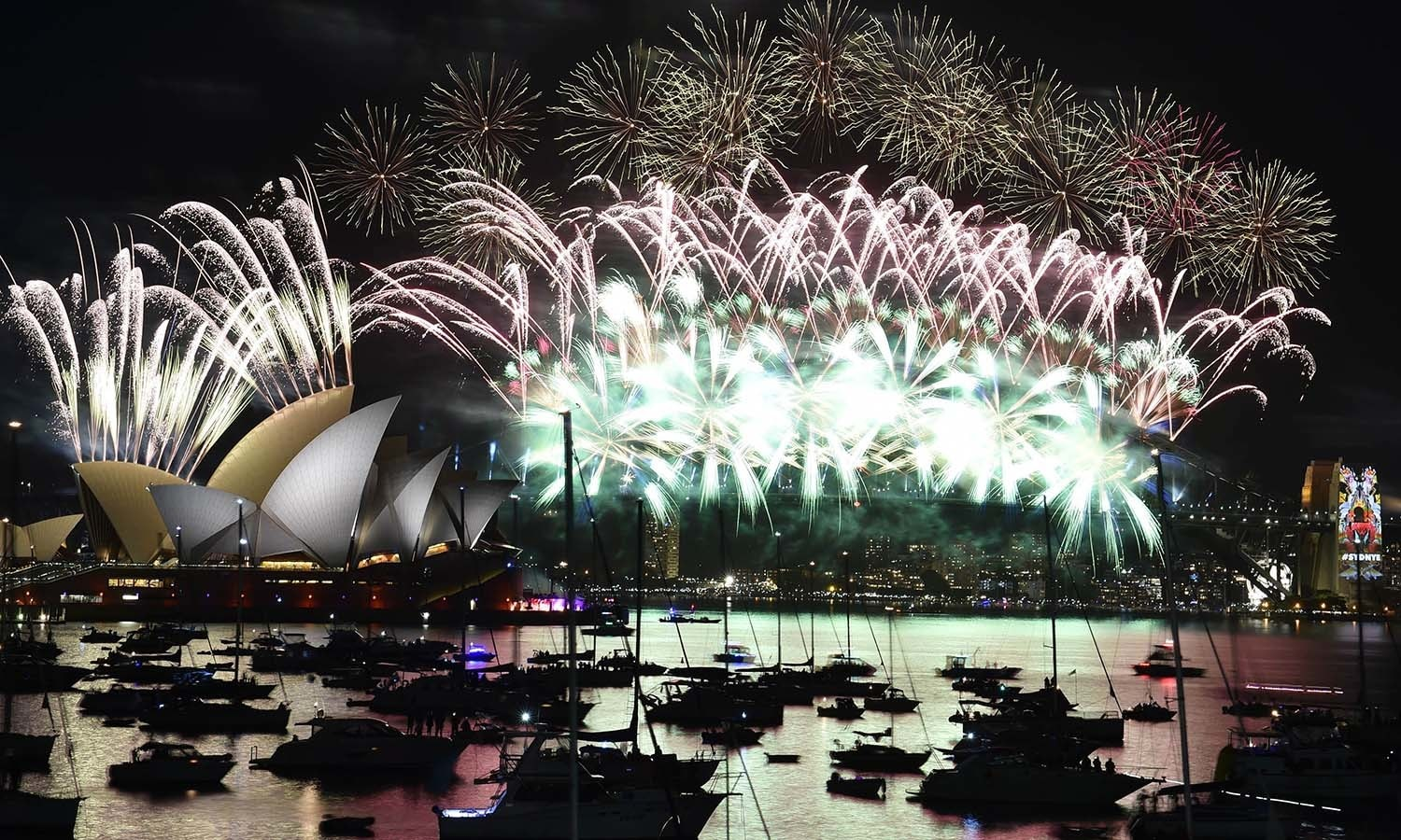 Fireworks light up the sky over Sydney's Opera House (L) and Harbour Bridge during New Year celebrations in Sydney on January 1, 2016.  AFP PHOTO / Saeed KHAN