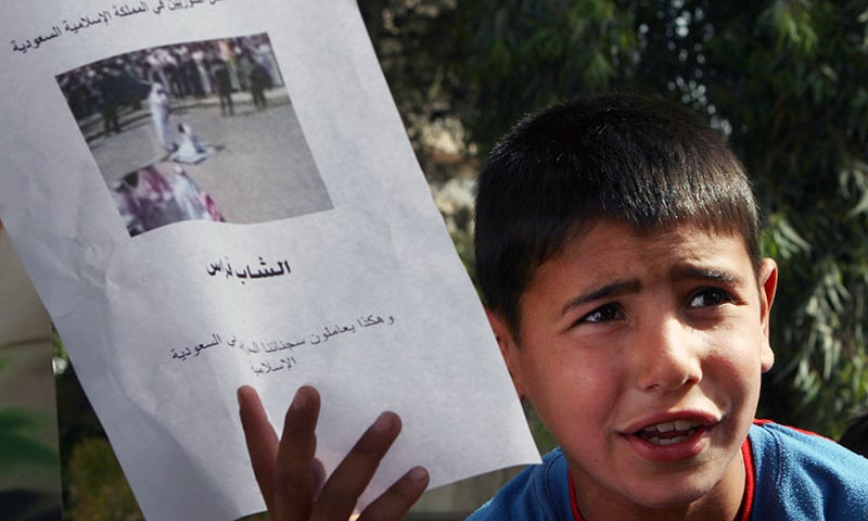 A Syrian boy holds up a photo of a beheading, at a rally in downtown Damascus, Syria to protest Saudi Arabia's beheading of two Syrians after being charged with drug trafficking. —AP/File