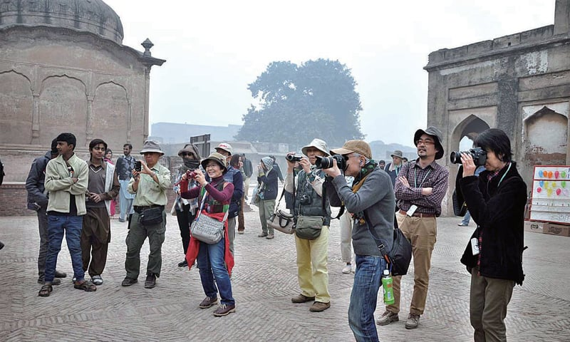 Members of a Japanese delegation capture rare moments during their visit to Lahore Fort on Friday. — APP