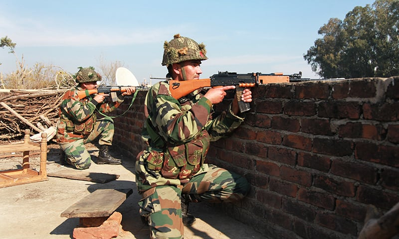Indian army soldiers take positions on a rooftop of a building outside the Indian airbase in Pathankot. —AP