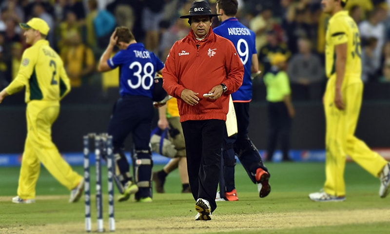 Pakistani umpire Aleem Dar (C) approaches to the stumps after the Pool A 2015 Cricket World Cup match between Australia and England at the Melbourne Cricket Ground. — AFP