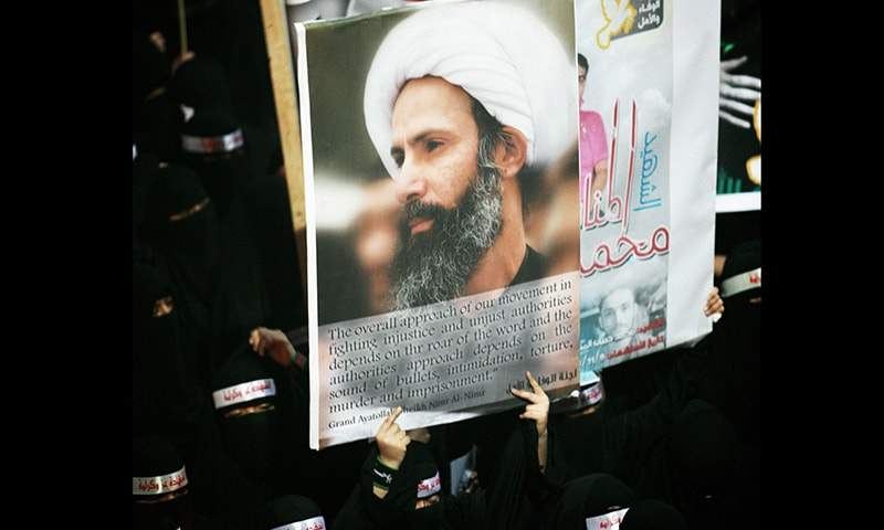 In this file photo, a Saudi anti-government protester carries a poster with the image of jailed Shia cleric Sheik Nimr al-Nimr during the funeral of three Shia Muslims allegedly killed by Saudi security forces in the eastern town of al-Awamiya. -AP/File