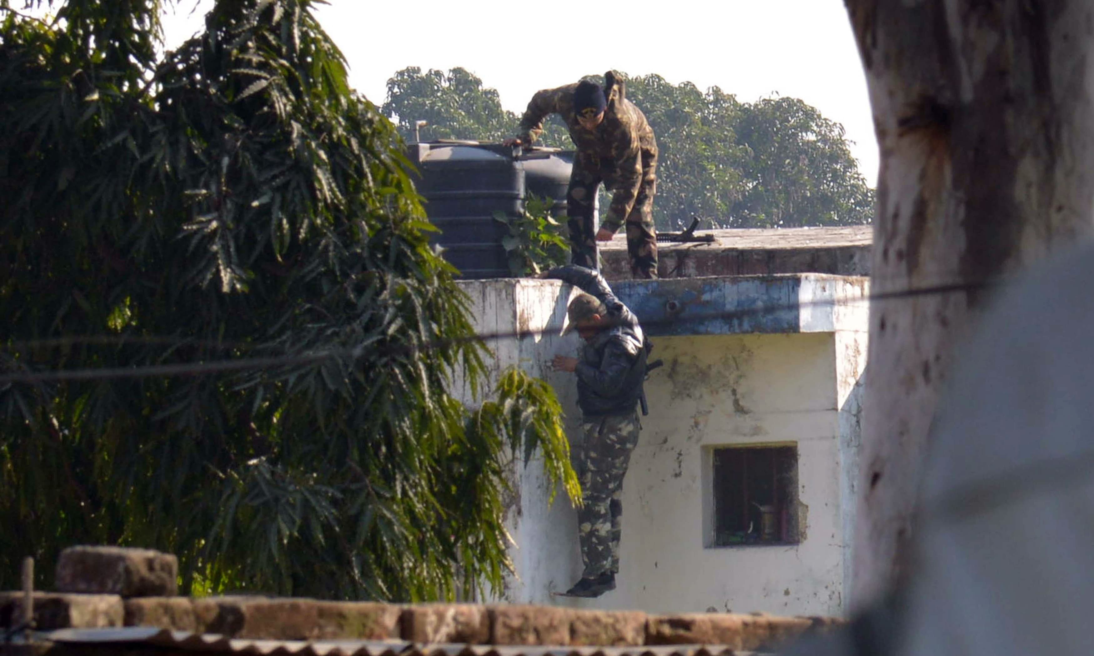 Indian security personnel position themselves on a rooftop at Pathankot air base. —AFP