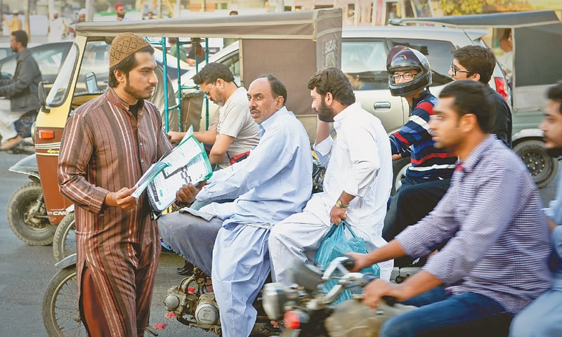 A Tanzeem-i-Islami activist leafleting in Karachi's PECHS locality on Saturday.—Fahim Siddiqi / White Star