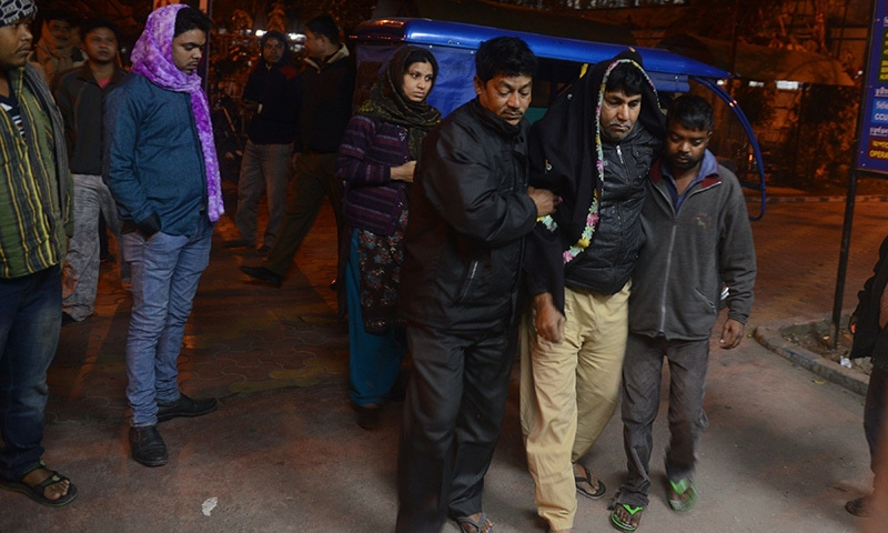 An injured resident (2nd R) is assisted upon his arrival for treatment at Siliguri Hospital following an earthquake in Siliguri on January 4, 2016.—AFP