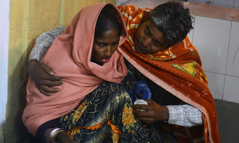 An injured Indian woman is comforted by her husband as she waits for treatment at Siliguri Hospital following an earthquake in Siliguri on January 4, 2016.-AFP