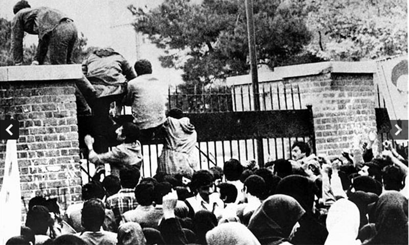 Iranian students climb over the wall of the US embassy in Tehran 04 November 1979. ─ AFP/File