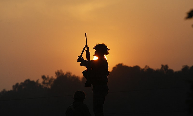 An Indian army soldier is silhouetted against the setting sun as he stands guard next to his colleague, sitting on the roof top of a house outside the Indian air force base in Pathankot. ─ AP