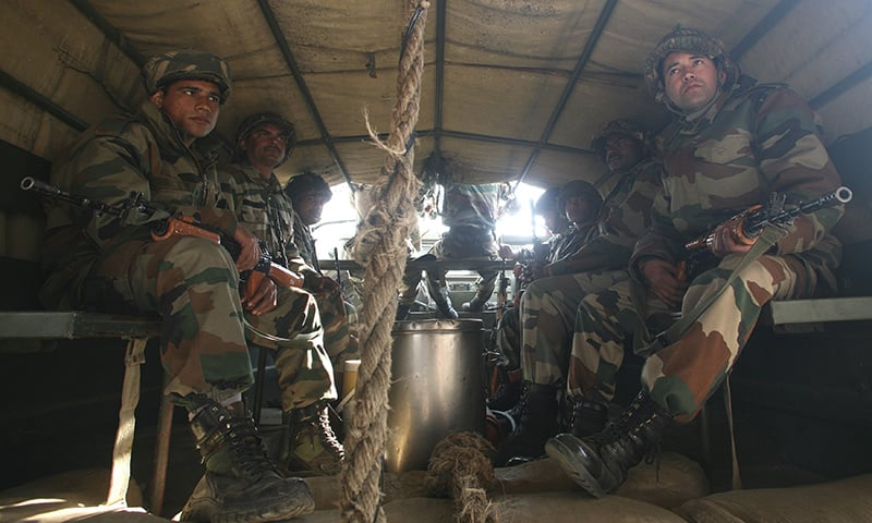 Indian army soldiers sit in a truck as they head towards the Indian Air Force (IAF) base at Pathankot. ─ Reuters