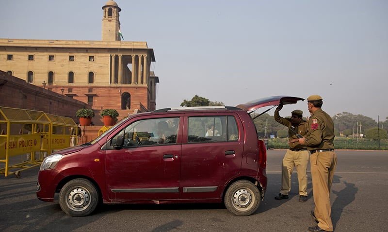 Indian policemen check a car near the Presidential Palace. ─ AP