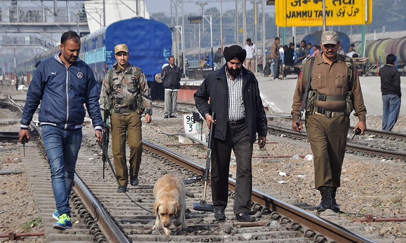 Indian police officials and dog squad members walk along railway tracks at a station in Jammu. ─ AFP