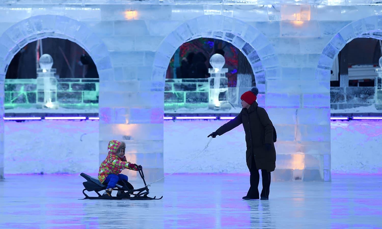 ایک بچہ اس فیسٹیول میں برف سے بنے ایک نمونے کے سامنے سے گزر کر رہا ہے — اے ایف پی