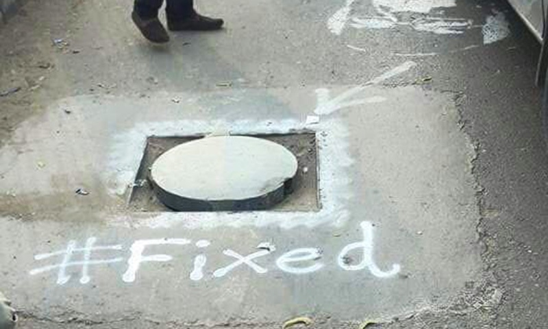 "The ""Fix it"" campaign activisits painted 'fixed' next to manholes they sealed. — Photo courtesy: Alamgir Khan"