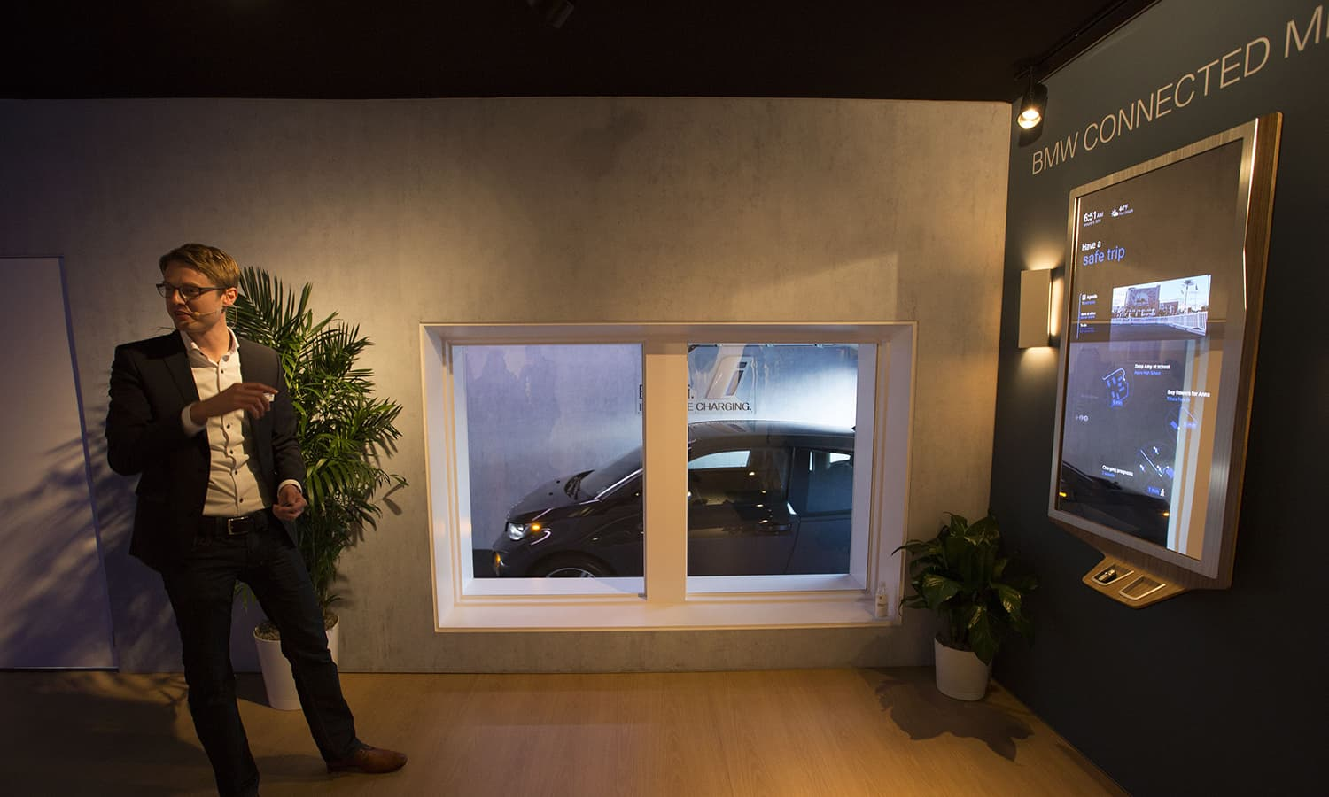 A BMW i3 electric car drives autonomously from a simulated garage where it had been automatically charged by an inductive charging station after an exhibitor simply picks up the keys from below the BMW Connected Mirror. — AFP