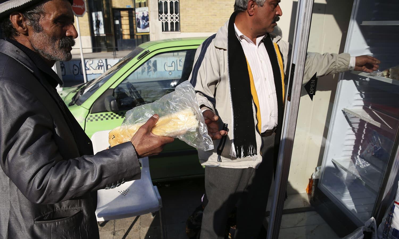In this Thursday, Jan. 7, 2016 photo, Iranian volunteer Mohammad Esmaeil Khosroabadi, right, donates a sandwich to a needy man at a street charity hut in southern Tehran, Iran. ─ AP
